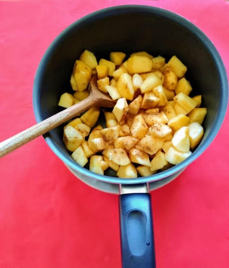 нарязаните ябълки в малка тенджерка