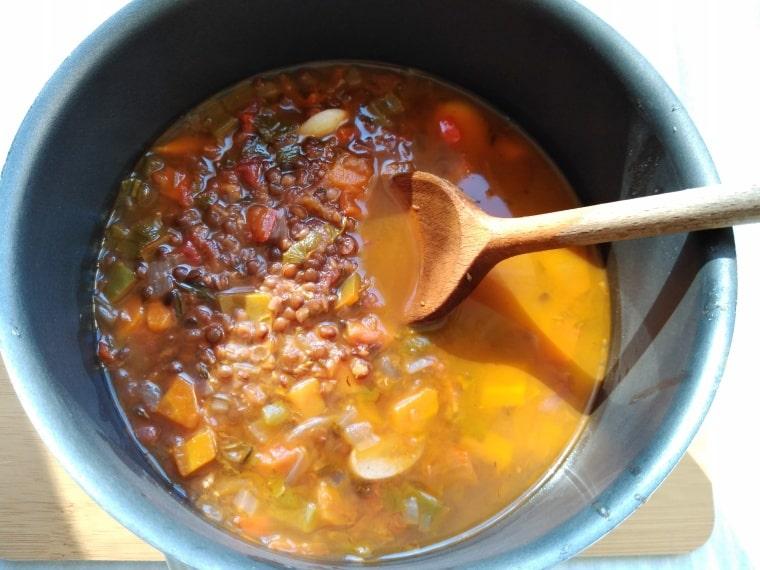 топла супа от черна леща и домати в тенджера