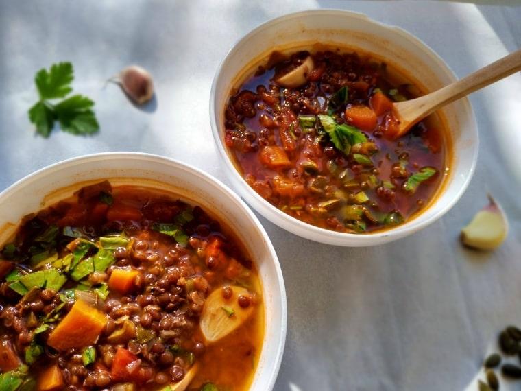 топла супа от черна леща и домати сипана в купички
